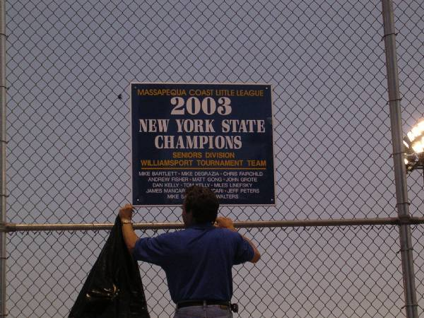 Manager of the State Championship Team unveils sign during ceremony at Burns Park