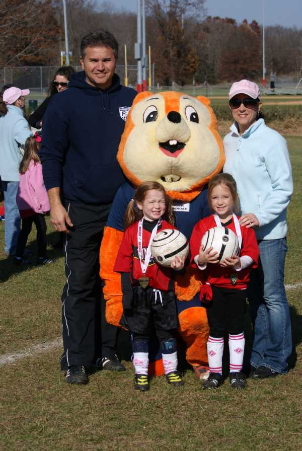 Coach and President Nick Genoese, Stephanie O'Donnell, and 'the girls' pose with USA Soccer Mascot, 'The Squirrel'