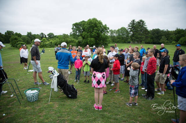 Pros showing kids the basics of the game of golf.